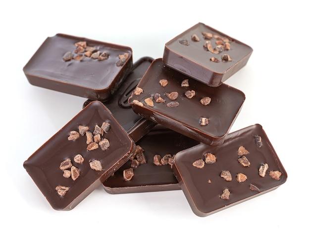 Carrés de chocolat noir aux amandes concassées sur un mur blanc