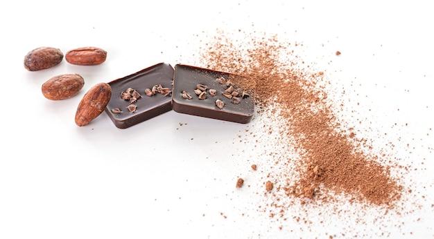 Carrés de chocolat noir avec des morceaux de fève de cacao torréfiée et de fève de cacao sur un mur blanc