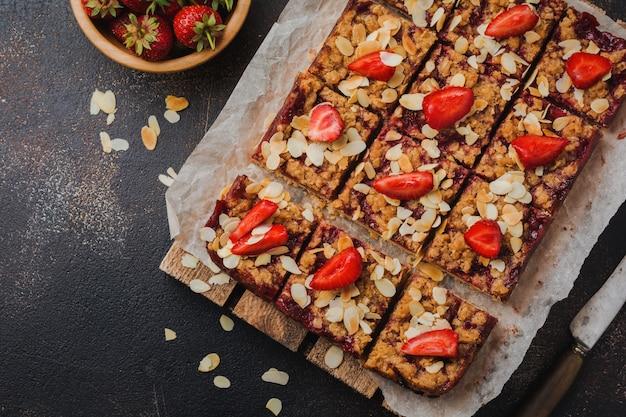 Carrés de dessert aux fraises et à l'avoine streisel sur la surface en béton de la plaque à pâtisserie ancienne sombre. style rustik