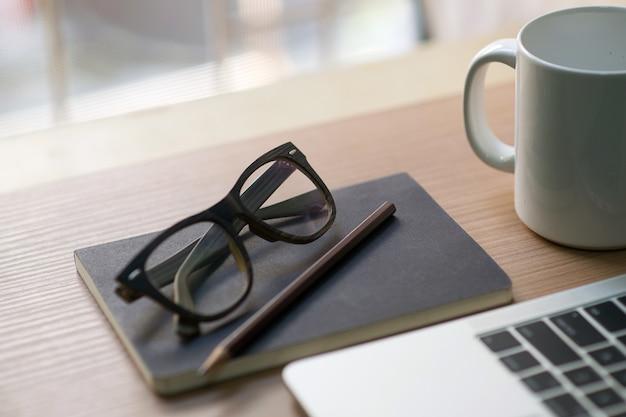 Carrière de l'écrivain sur le bureau avec des tasses à café blanches, des cahiers, des crayons et des lunettes