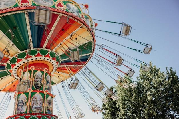 Carrousel avec des chaînes dans un parc d'attractions par une journée ensoleillée d'été