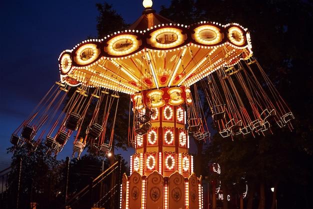 Carrousel dans un parc d'attractions dans la ville de nuit