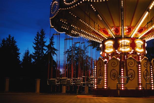 Carrousel manège dans un parc d'attractions dans la ville de nuit