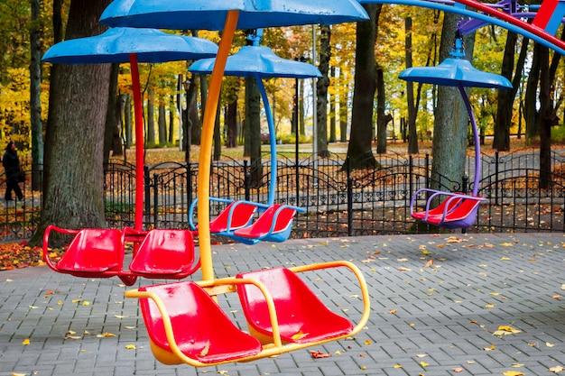 Carrousel vide avec sièges suspendus sur des chaînes sans attendre les visiteurs.