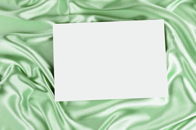 Carte d'affiche en toile blanche vierge pour texte de voeux sur un mur de tissu de soie drapé de couleur verte. vue de dessus