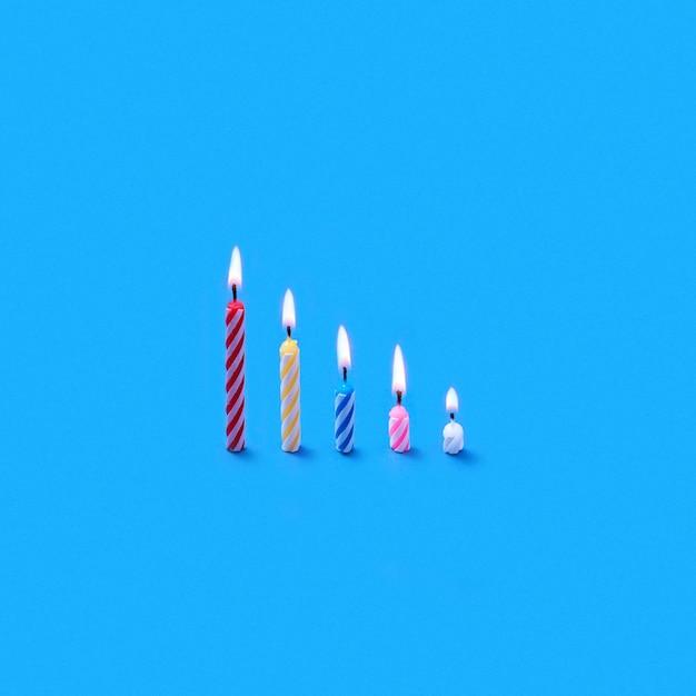 Carte d'anniversaire de voeux de bougies debout verticalement de différentes hauteurs pour dessert sucré et gâteaux