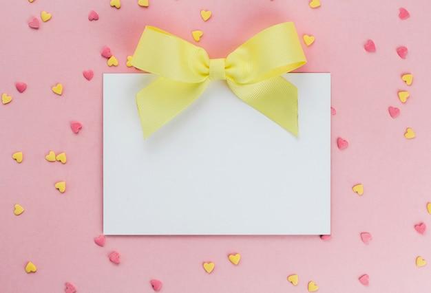 Carte avec un arc jaune sur un fond de confettis confiserie en forme de coeur sur un espace de copie de fond rose