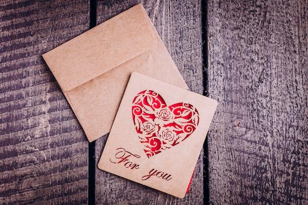Carte artisanale pour la saint valentin sur fond de table en bois. texte 'pour toi