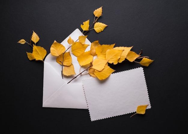 Carte d'automne avec feuillage jaune sur fond noir. enveloppe avec une feuille de papier vierge blanche. place pour le texte promotionnel ou de salutations