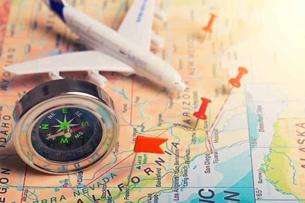 La carte, l'avion et des trucs sur une table en bois. vue de dessus