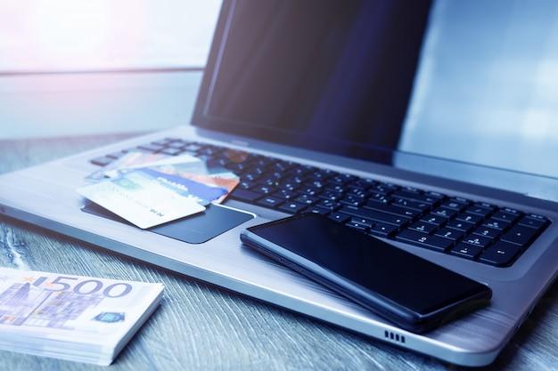 Carte bancaire, ordinateur portable, smartphone, euro