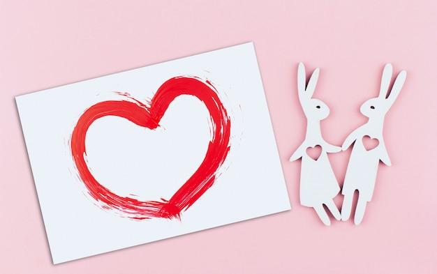 Carte blanche avec un coeur rouge peint et un couple de lapin avec des coeurs dans leur poitrine sur un espace de copie de fond rose
