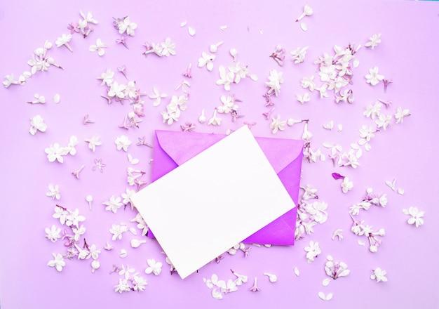 Une carte blanche avec une enveloppe rose pour les lettres, allongée sur un fond clair et des fleurs de lilas blanc dans des tons roses.