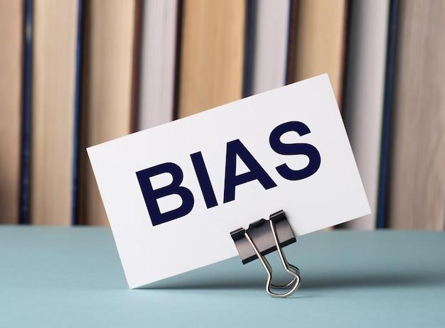 Une carte blanche avec le texte bias se dresse sur un clip pour papiers sur la table sur fond de livres. défocaliser