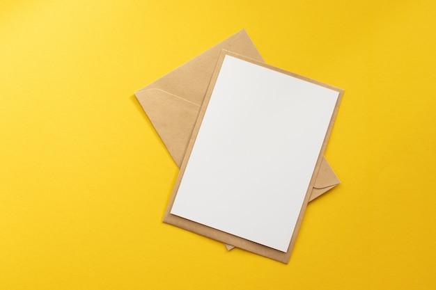 Carte blanche vierge avec modèle d'enveloppe en papier kraft brun simulé sur fond jaune