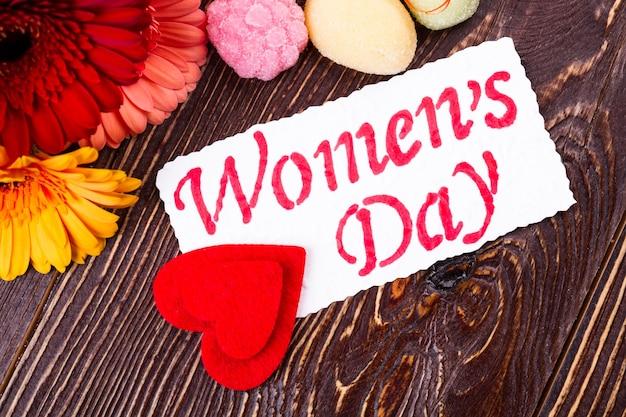 Carte et bonbons de la fête de la femme. coeurs et gerberas sur bois. surprenez votre dame avec un cadeau. goût sucré des vacances des femmes.