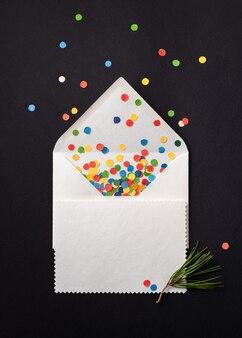 Carte-cadeau de noël sur enveloppe blanche avec des confettis festifs. remarque feuille de papier sur fond noir