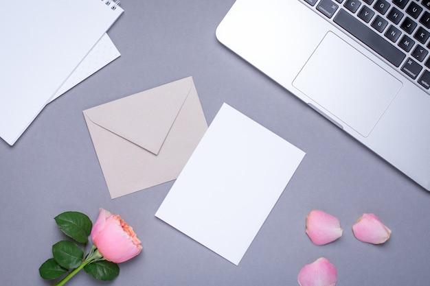 Carte-cadeau avec rose rose et ordinateur portable sur gris