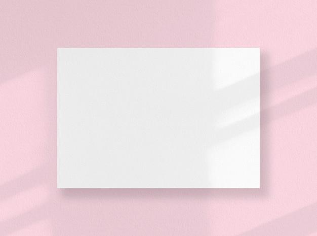 Carte carrée vierge, feuille blanche comme maquette avec des ombres ensoleillées sur une surface rose