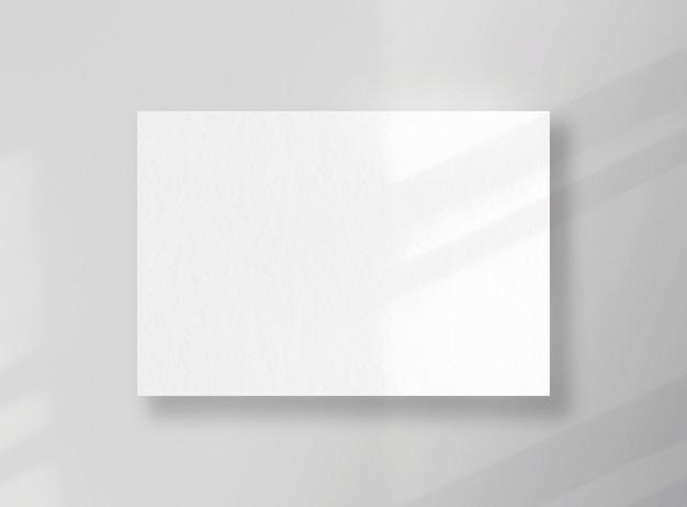 Carte carrée vierge, feuille comme maquette avec des ombres ensoleillées sur une surface grise