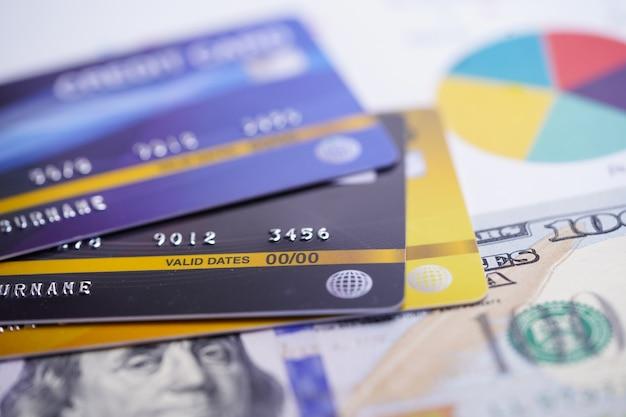 Carte de crédit avec un billet en dollars américains sur du papier quadrillé.