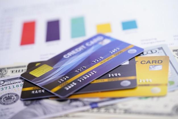 Carte de crédit avec des billets en dollars américains sur du papier millimétré.