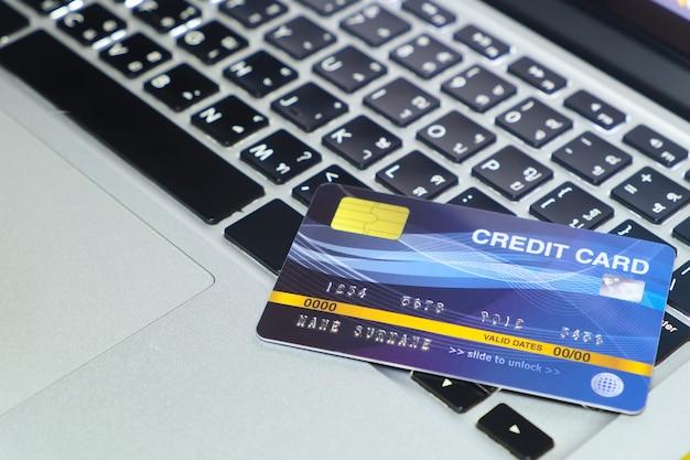Carte de crédit bleue en mode verrouillé, mise sur le clavier de l'achat en ligne d'un ordinateur portable moderne et paiement par carte de crédit