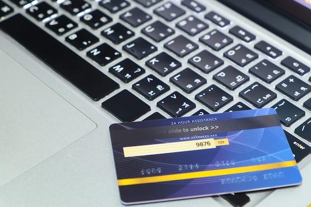 Carte de crédit bleue en mode verrouillé, mise sur le clavier d'un ordinateur portable moderne, achats en ligne et paiement via le concept de carte de crédit