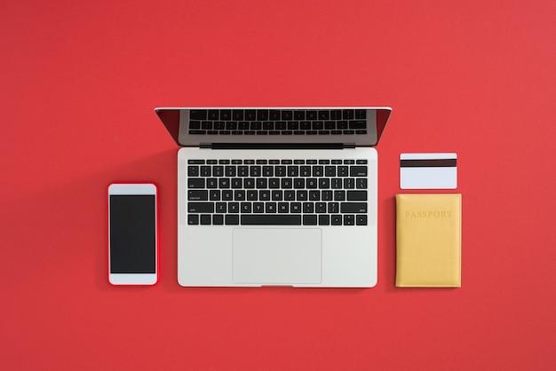 Carte de crédit, clavier et passeport sur table rouge à plat, espace de copie. paiement des voyages de vacances en ligne.