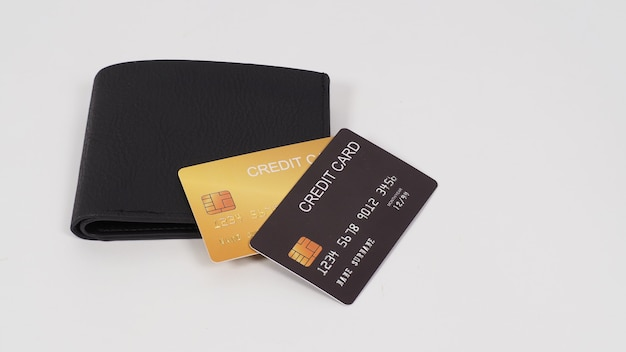 Carte de crédit couleur noir et or en noir sur portefeuille isolé sur fond blanc.