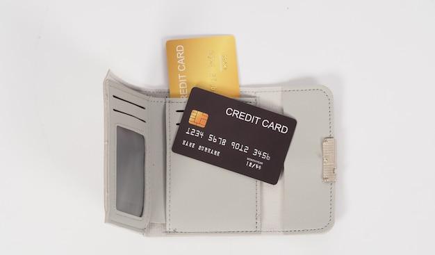 Carte de crédit couleur noir et or avec portefeuille gris isolé sur fond blanc.