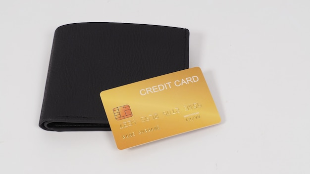 Carte de crédit couleur or en noir sur portefeuille isolé sur fond blanc.