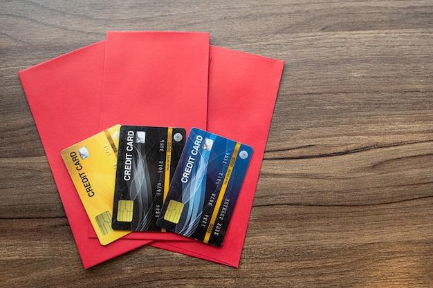 Carte de crédit dans une enveloppe rouge pour le bonus du festival du nouvel an chinois sur fond de table en bois.