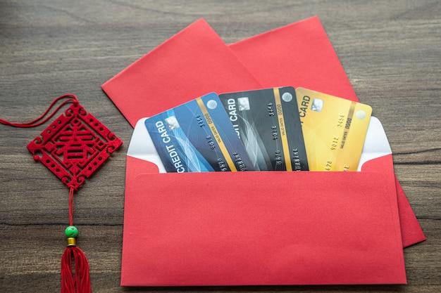Carte de crédit dans une enveloppe rouge avec le texte chinois bénédictions écrites dessus est un bonus de printemps pour le festival du nouvel an chinois sur fond de table en bois.