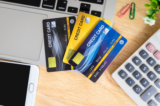Carte de crédit dans le panier d'achat avec ordinateur portable, ordinateur portable, arbre de pot de fleur, smartphone et calculatrice sur fond en bois, services bancaires en ligne table de bureau vue de dessus.
