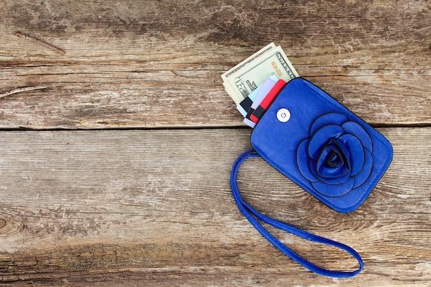 Carte de crédit et dollars en portefeuille sur fond de bois. vue de dessus.