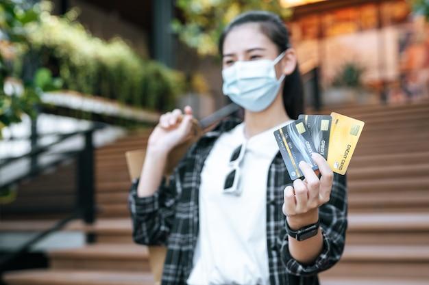 Carte de crédit à mise au point sélective dans la main d'une jeune femme asiatique en masque de protection debout dans les escaliers du centre commercial