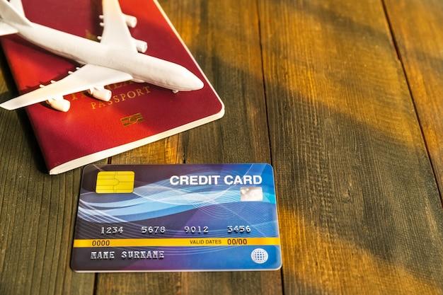 Carte de crédit mise sur un bureau en bois avec passeport et plan, préparation au concept de voyage