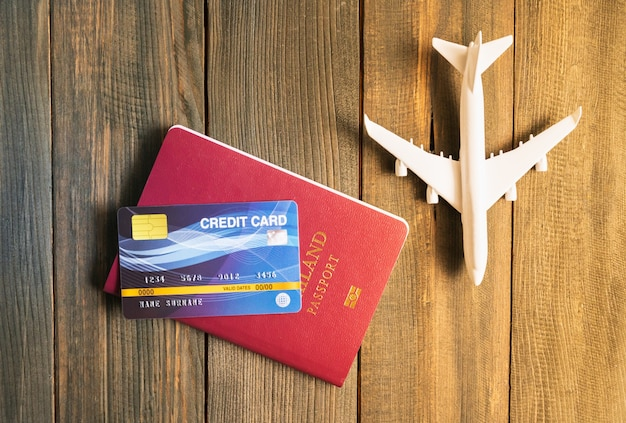 Carte de crédit mise sur le passeport et le modèle d'avion sur table en bois, préparation au concept de voyage