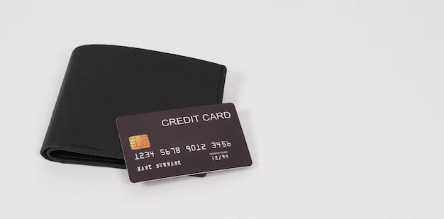 Carte de crédit noir sur portefeuille isolé sur fond blanc.