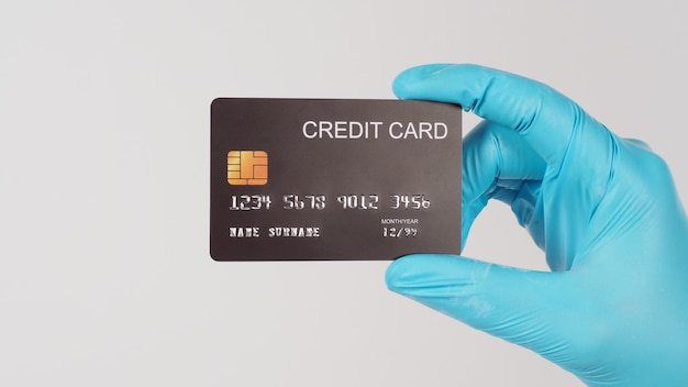 Carte de crédit noire en main avec un gant médical bleu sur fond blanc.coup de côté