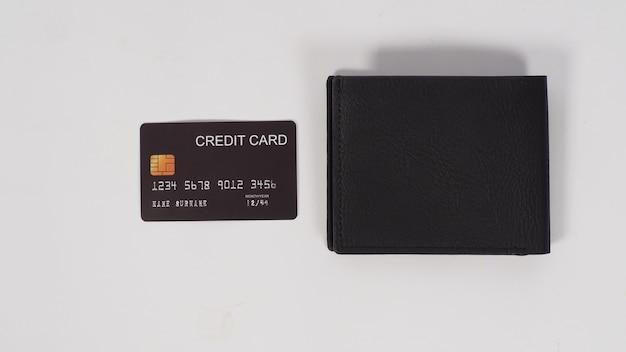 Carte de crédit noire et portefeuille noir sur fond blanc.