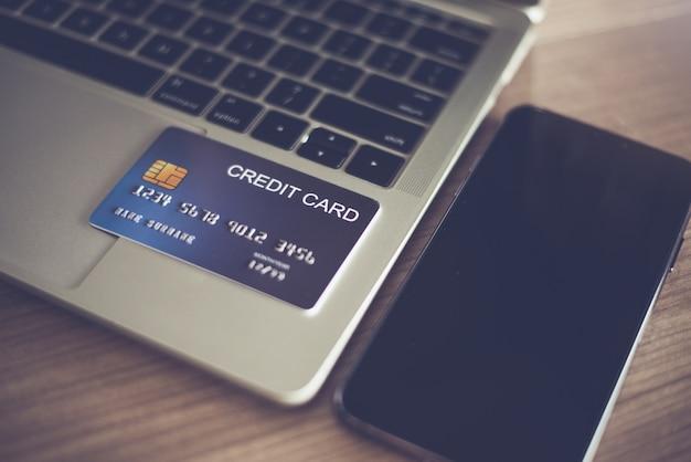 La carte de crédit sur un ordinateur portable et un smartphone