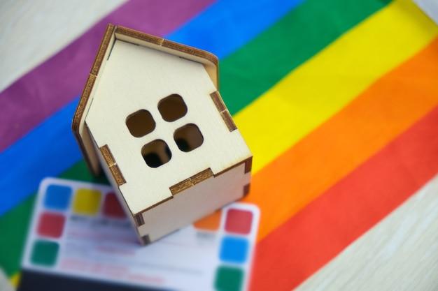 Carte de crédit et une petite maison sur le drapeau de la communauté lgbt