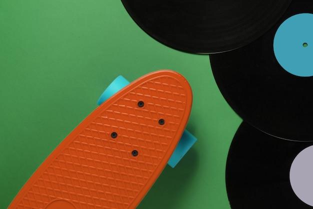 Carte cruiser et disques vinyles sur fond vert. concept de style rétro de la jeunesse. années 80. vue de dessus