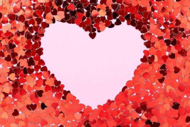 Une carte décorée de motifs coeurs rouges, saint valentin. cartes de célébration sur fond rose avec espace de copie pour votre texte. bannière.