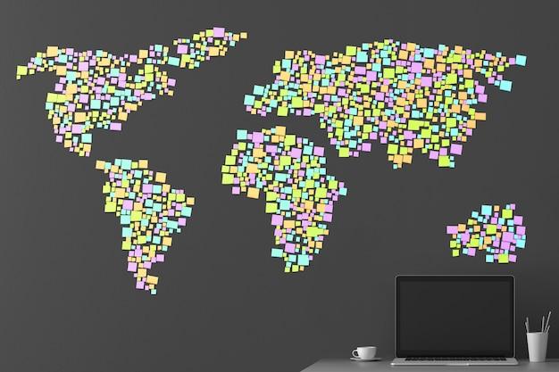 Carte du monde d'après les autocollants collés au mur avec un ordinateur portable debout