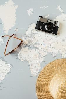 Carte du monde minimale avec épingles, appareil photo rétro, lunettes de soleil, chapeau de paille