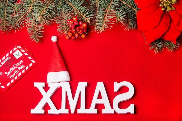 Carte du nouvel an chapeau de père noël et lettre postale sur fond rouge