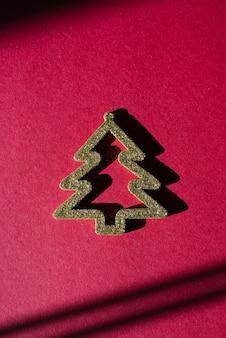 Carte élégante minimaliste de noël. arbre de noël or stylisé avec ombre dure. la vue d'en haut. tendance